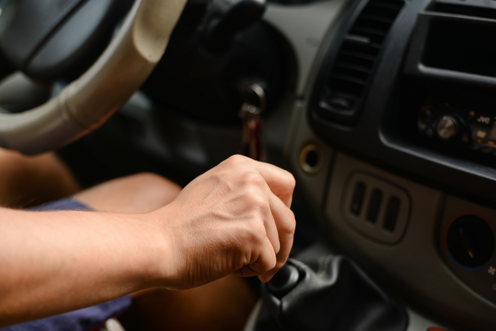 Picture close up driver's right hand shifting the gear stick in car