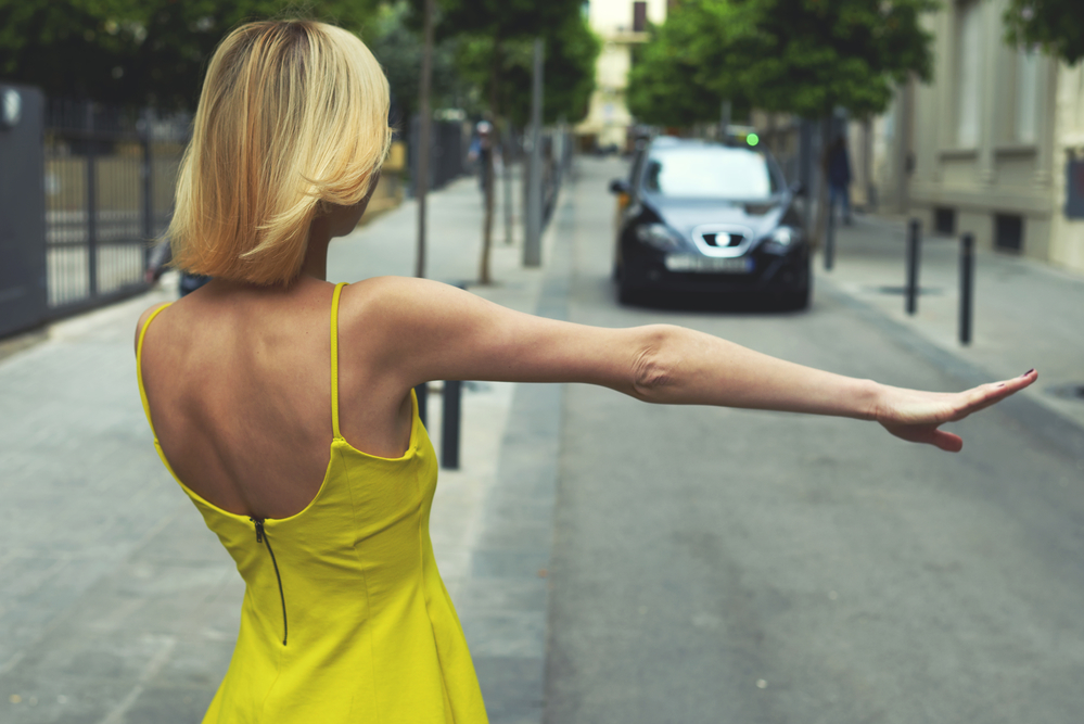 woman in yellow dress hailing a car cab taxi.