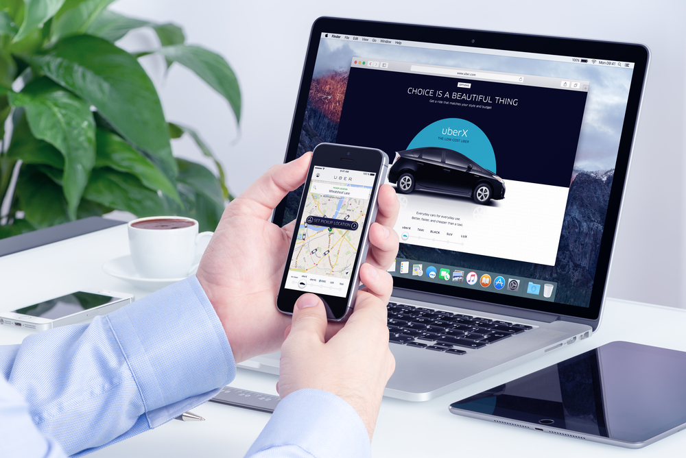 Man orders Uber X through his iPhone and Macbook.
