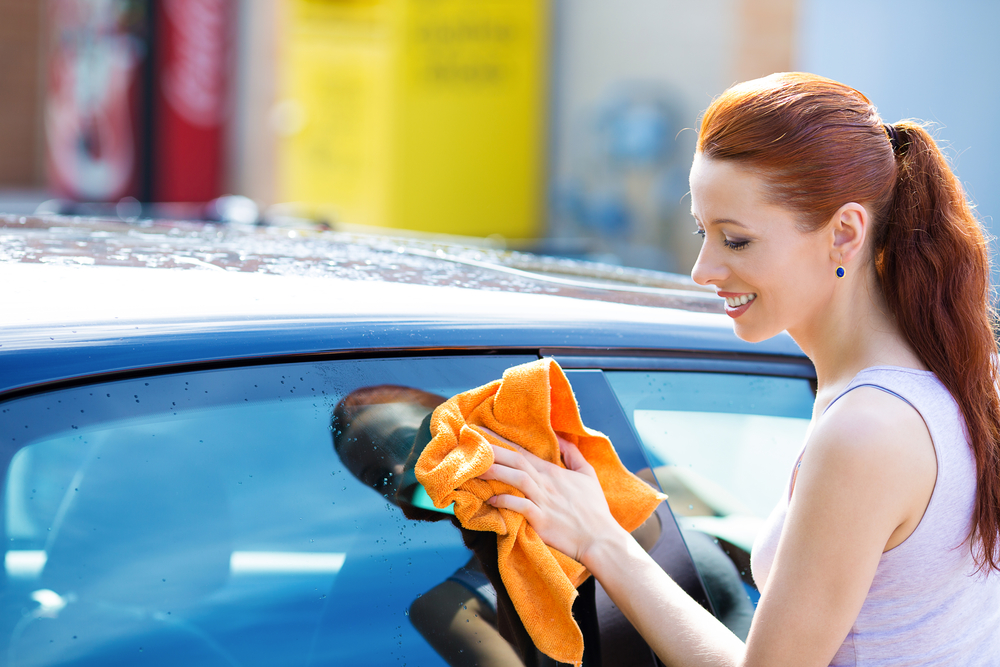 Woman cleaning , dry wiping her black car on summer sunny day