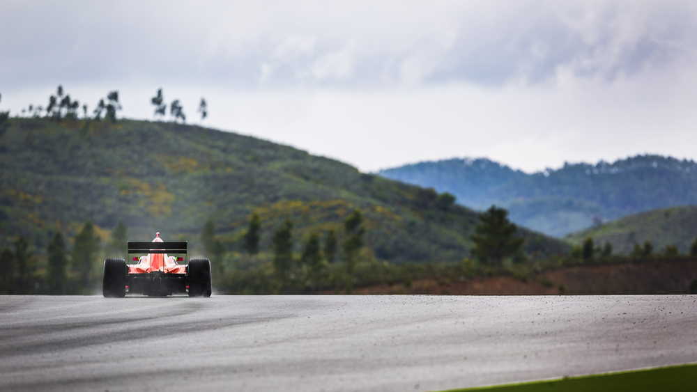 Motorsport driver drives in the rain in a beautifull landscape of hills. with the spray of rain behind the car.