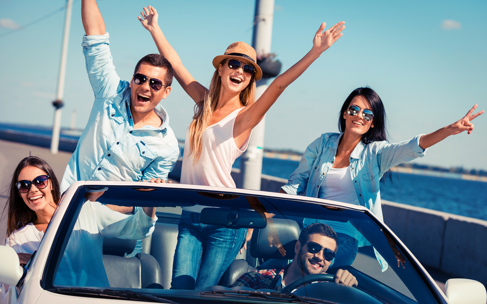 Friends in convertible. Group of young happy people enjoying road trip in their white convertible and raising their arms