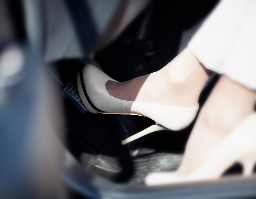 A woman's foot pumping the brake pedal of a car.