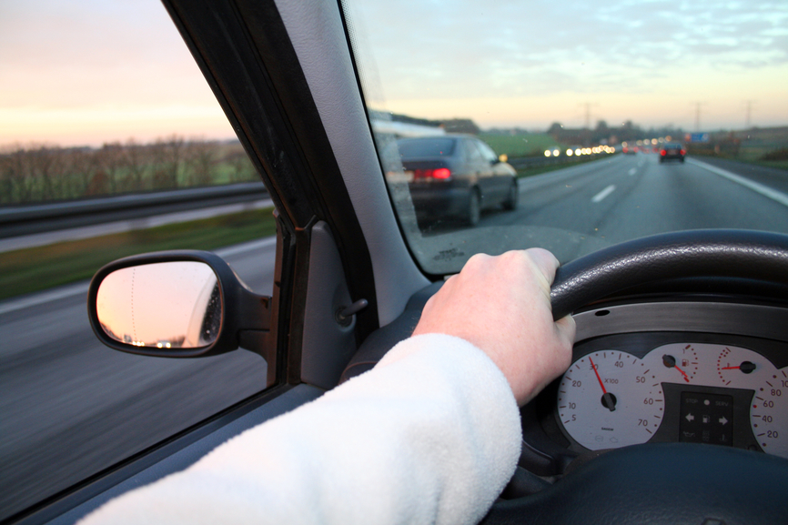driving steering car. hand holding wheel whilst car overtaking. drive at dusk with sunset in horizon