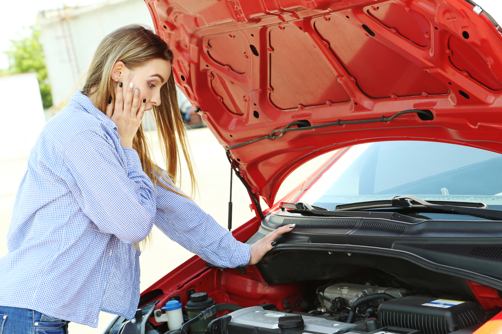 Beautiful young girl open hood of broken car