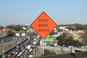 Orange Road Work Ahead Sign showing traffic jam behind in soft focus