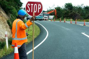 KAITAIA, NZ - NOV 05:Road worker slows traffic with stop sign on Nov 05 2013.The Road Maintenance crew has the responsibility for the day-to-day maintenance needs of the road system.