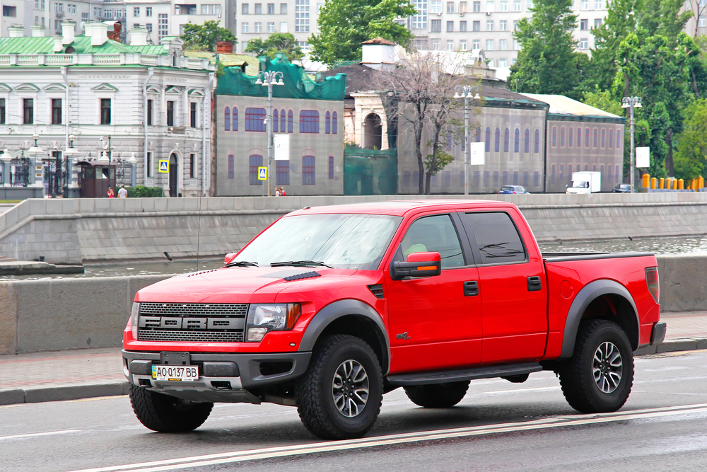 Red pickup truck Ford F-150 Raptor at the city street.
