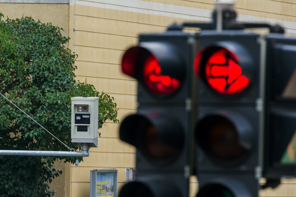 the red light of a traffic signal is monitored by a red light camera.