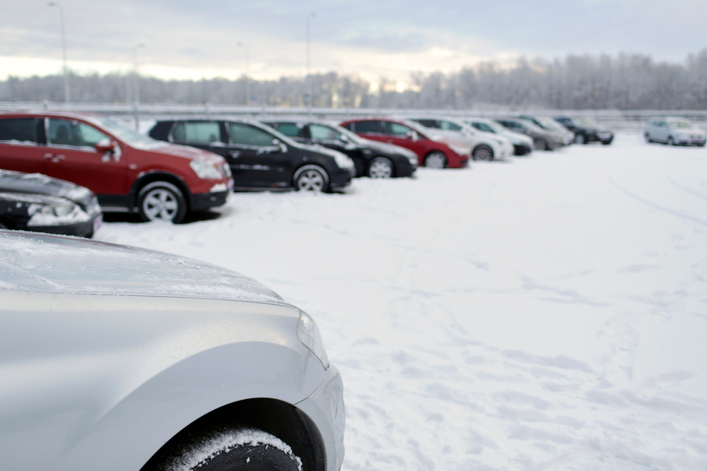 transportation, winter and vehicle concept - car parking with snow