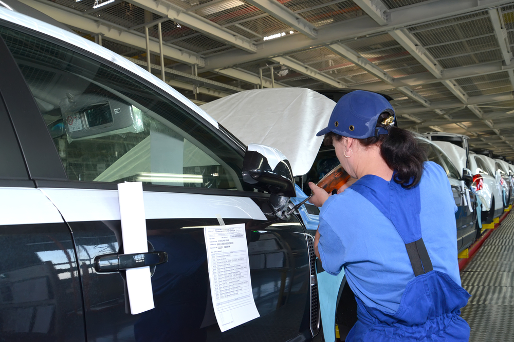 The female collector fixes a mirror on a car body by means of the screw gun. Assembly conveyor of automobile plant