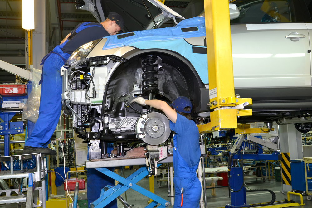 Workers install the engine on the car. Assembly conveyor of automobile plant