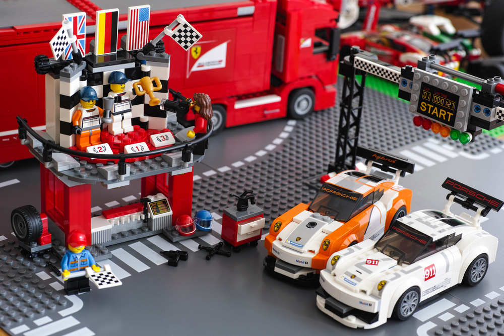 2015 Winning podium with two drivers and photographer in Porsche 911 GT Finish Line by LEGO Speed Champions with starting lights, flag-raising function and 2 cars. Studio shot.