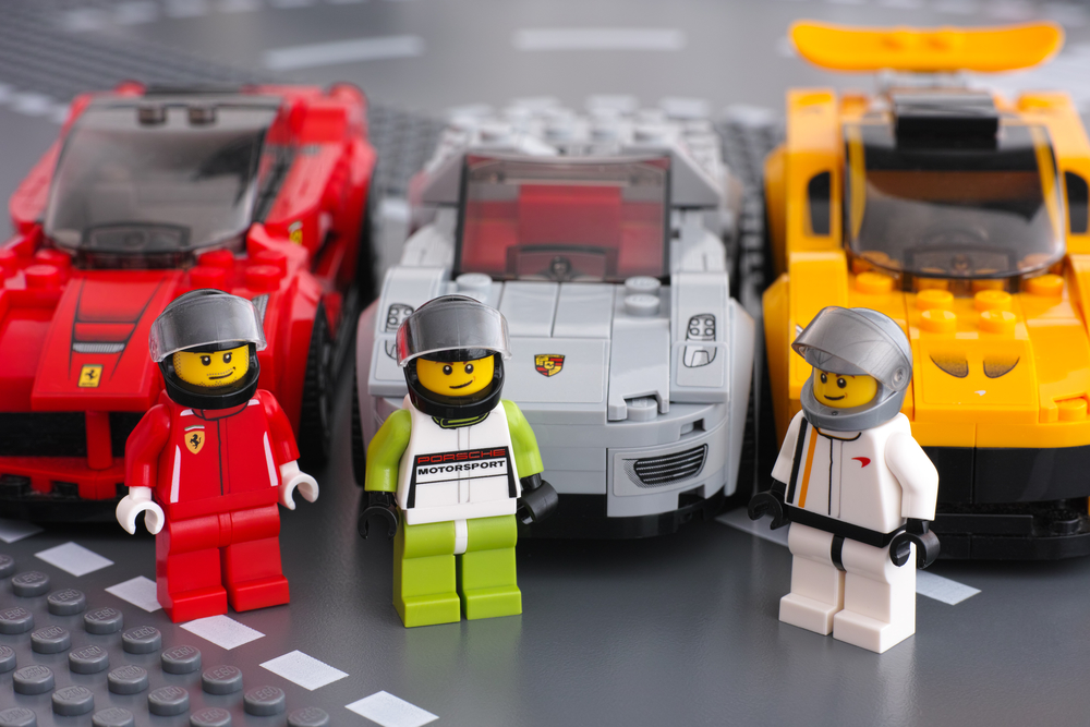2015 Lego drivers minifigures by LEGO Speed Champions and his car on background. There are Lego LaFerrari, Lego Porsche 918 Spyder and Lego McLaren P1 cars. Studio shot.