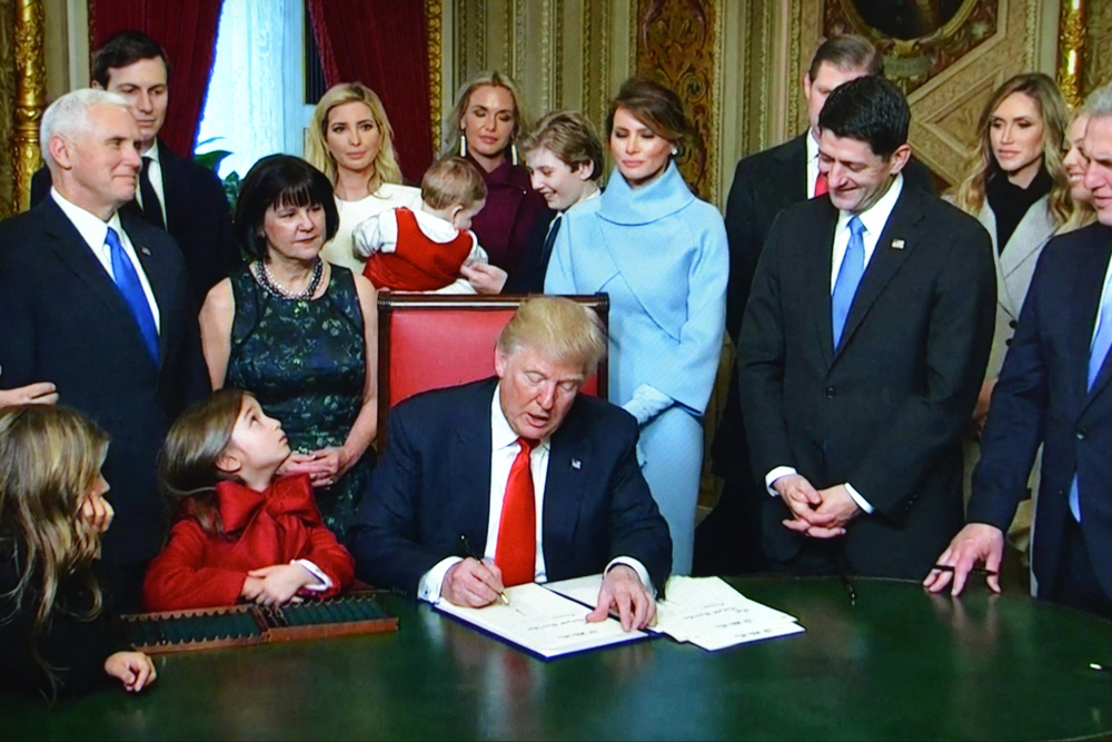 Washington DC, USA - January 20, 2017: An internet live news channel streams President Trump signing executive orders following his inauguration.