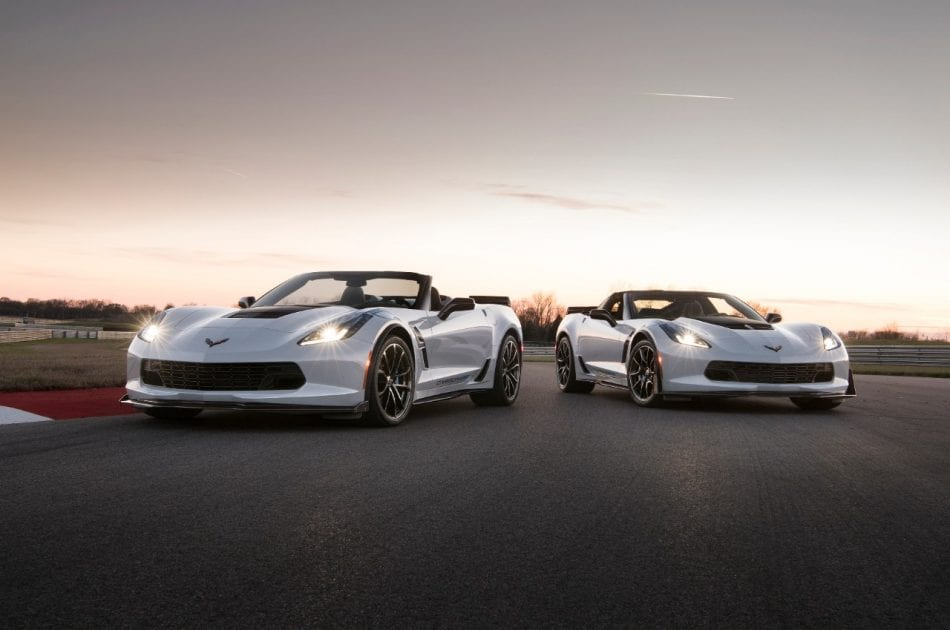 Two White Chevrolet Corvettes in road at night