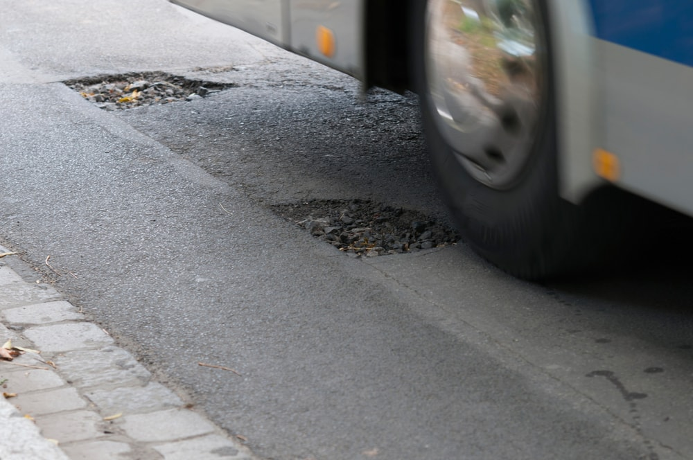 car-driving-over-asphalt-potholes-min