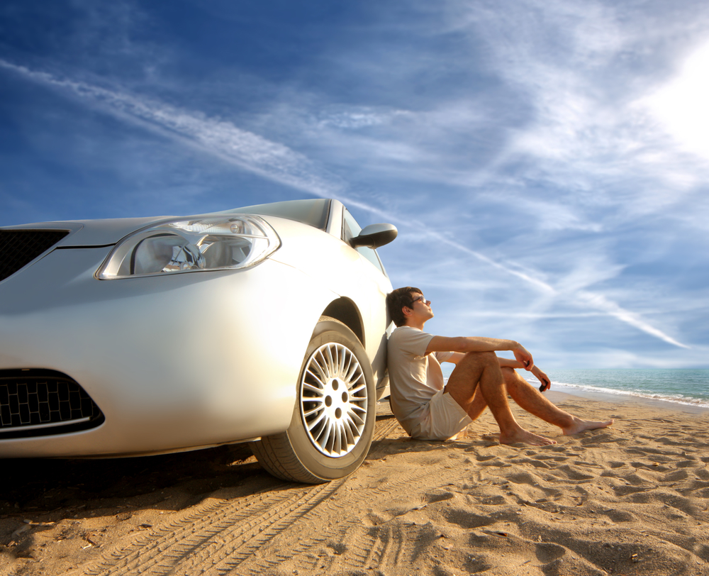 Person sitting on ground leaning on white car