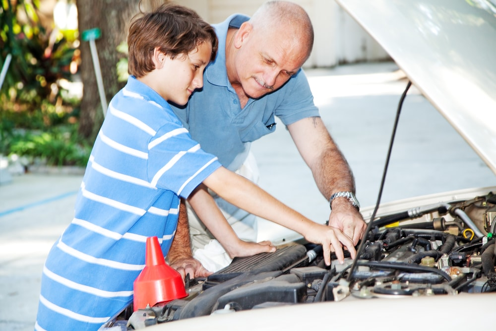 gransfather and son fixing a car together