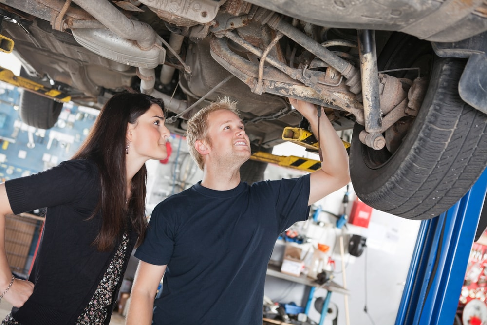 man and woman fixing a car together