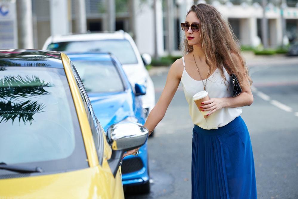 ridesharing woman passenger enters yellow car
