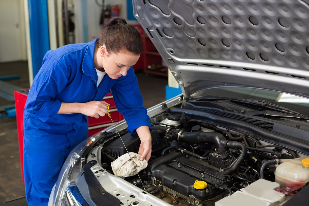 woman checking engine oil